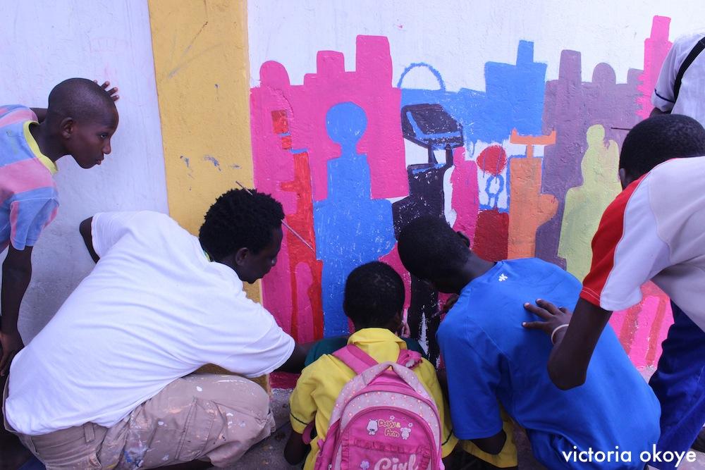 Musah Swallah, artist et membre de NMA, peinte avec des jeunes.